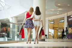 Dwa dziewczyny na zakupy chodzą na zakupy centrum handlowym z torbami Zdjęcia Stock