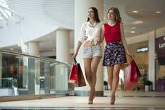 Dwa dziewczyny na zakupy chodzą na zakupy centrum handlowym z torbami Zdjęcie Royalty Free