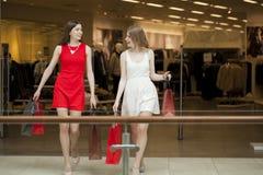 Dwa dziewczyny na zakupy chodzą na zakupy centrum handlowym z torbami Fotografia Royalty Free