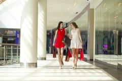 Dwa dziewczyny na zakupy chodzą na zakupy centrum handlowym z torbami Fotografia Stock