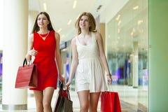 Dwa dziewczyny na zakupy chodzą na zakupy centrum handlowym z torbami Obrazy Stock