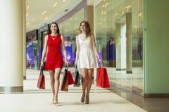Dwa dziewczyny na zakupy chodzą na zakupy centrum handlowym z torbami Zdjęcia Royalty Free