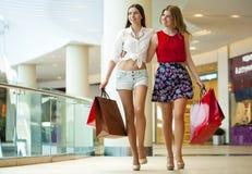 Dwa dziewczyny na zakupy chodzą na zakupy centrum handlowym z torbami Obrazy Royalty Free