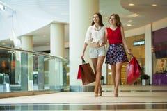 Dwa dziewczyny na zakupy chodzą na zakupy centrum handlowym z torbami Obraz Stock