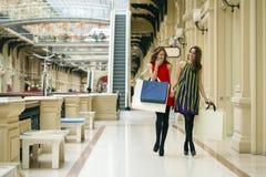 Dwa dziewczyny na zakupy chodzą na zakupy centrum handlowym z torbami Zdjęcie Stock