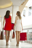 Dwa dziewczyny na zakupy chodzą w zakupy centrum handlowym z torbami Fotografia Stock
