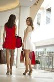 Dwa dziewczyny na zakupy chodzą w zakupy centrum handlowym z torbami Obrazy Stock