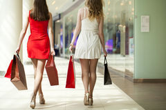 Dwa dziewczyny na zakupy chodzą w zakupy centrum handlowym z torbami Zdjęcia Stock