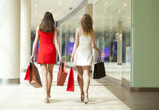 Dwa dziewczyny na zakupy chodzą w zakupy centrum handlowym z torbami Obraz Royalty Free