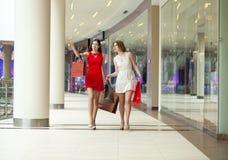 Dwa dziewczyny na zakupy chodzą w zakupy centrum handlowym z torbami Zdjęcia Royalty Free