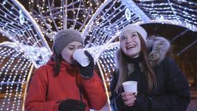 Dwa dziewczyny na zima wieczór spacerują w centrum miasta, dekorują dla bożych narodzeń z jaskrawymi girlandami i światłami giro zbiory