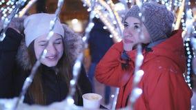 Dwa dziewczyny na zima wieczór spacerują w centrum miasta, dekorują dla bożych narodzeń z jaskrawymi girlandami i światłami zbiory