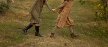 Dwa dziewczyny, nastolatkowie, trzyma ręki, chodzą na zielonej trawie, boczny widok bieg w naturze zdjęcia stock