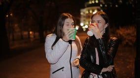 Dwa dziewczyny nocy outside zaświecający lampami miasto, pije kawę od papierowych filiżanek i opowiadać zbiory