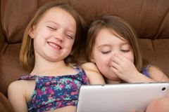 Dwa dziewczyny ogląda śmiać się i pastylkę obrazy stock