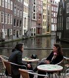 Dwa dziewczyny opowiada przy bruk kawiarnią blisko kanału w Amsterdam obrazy stock