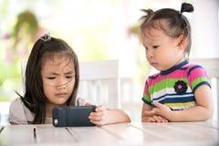 Dwa dziewczyny poważny azjatykci obsiadanie na krzesło przyglądającym telefonie komórkowym Obraz Stock