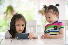 Dwa dziewczyny poważny azjatykci obsiadanie na krzesło przyglądającym telefonie komórkowym Fotografia Stock