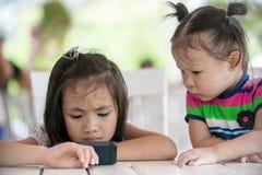 Dwa dziewczyny poważny azjatykci obsiadanie na krzesło przyglądającym telefonie komórkowym Zdjęcie Royalty Free