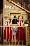 Dwa dziewczyny pozują w drzewnym domu Fotografia Royalty Free