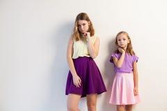 Dwa dziewczyny pozuje z jaskrawymi modnymi sukniami na białym tle Zdjęcia Stock