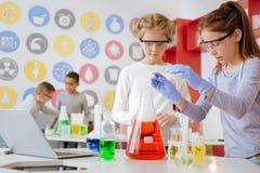 Dwa dziewczyny prowadzi chemicznego eksperyment w szkolnym lab zdjęcie royalty free