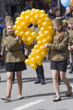 Dwa dziewczyny przy paradą z balonami w formie cyfra dziewięć ( Fotografia Stock
