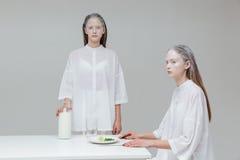 Dwa dziewczyny przy stołem ma posiłek Zdjęcie Royalty Free