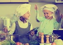 Dwa dziewczyny przygotowywa warzywa i ono uśmiecha się indoors Obrazy Stock
