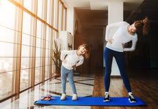 Dwa dziewczyny różni wieki robi joga Zdjęcia Stock