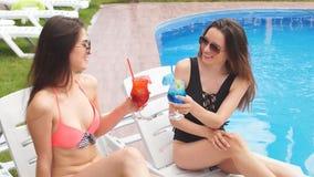 Dwa dziewczyny relaksuje basenem i pije świeżego koktajl wydają czas zdjęcie wideo