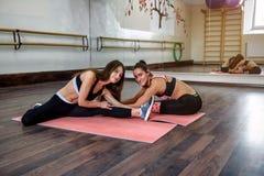 Dwa dziewczyny robią joga, aerobiki, pilates ćwiczenia fotografia royalty free