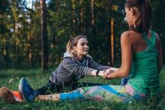 Dwa dziewczyny robi partnera rozciągania joga ćwiczeniu, Paschimottanasana lub sadzającej przedniej chył pozie, działanie outdoor zdjęcia stock