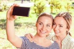 Dwa dziewczyny robi selfie w parku Zdjęcie Stock