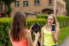 Dwa dziewczyny są bloggers Młodzi dziennikarzi Opisuje przewagi telefon Robi transmisi na internecie Dokumentacyjny vlog obrazy royalty free