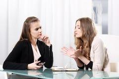 Dwa dziewczyny siedzi przy stołem Fotografia Stock