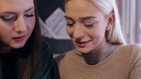 Dwa dziewczyny siedzi w kawiarni z telefonem w ręce zbiory