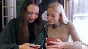 Dwa dziewczyny siedzi w kawiarni z telefonem w ręce zbiory wideo