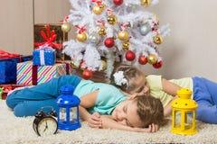 Dwa dziewczyny spali przez całej nowy rok wigilii przy choinką podczas gdy czekający przyjazd Święty Mikołaj i prezenty Zdjęcie Royalty Free