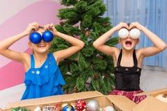 Dwa dziewczyny stawiają duże Bożenarodzeniowe piłki ich oczy fotografia royalty free