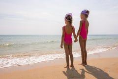 Dwa dziewczyny stoi na plaży i spojrzeniu przy horyzontem w kostiumach kąpielowych Fotografia Stock