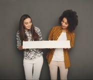 Dwa dziewczyny trzyma pustego białego sztandar zdjęcie royalty free