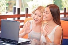 Dwa dziewczyny używa laptop w kawiarni zdjęcie stock