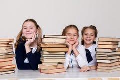 Dwa dziewczyny uczennicy siedzą z książkami przy jego biurkiem na lekcji przy szkołą zdjęcia stock
