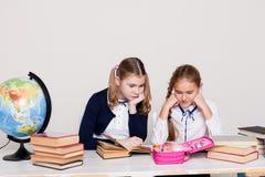 Dwa dziewczyny uczennicy siedzi przy jego biurkiem na lekcji przy szkołą obrazy royalty free