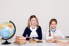 Dwa dziewczyny uczennicy siedzi przy jego biurkiem na lekcji przy szkołą obrazy stock