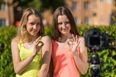 Dwa dziewczyny w lecie w parku Młodzi dziewczyn bloggers pokazuje gesty ręki OK Emocjonalnie wideo transmisja obraz stock