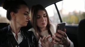 Dwa dziewczyny w tylnym siedzeniu samochodowego udzielenia telefonu komórkowego seansu parawanowa zawartość Przyjaciele wpólnie j zdjęcie wideo