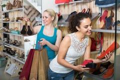 Dwa dziewczyny wybiera buty w sklepie Zdjęcie Stock