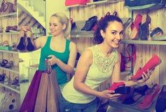 Dwa dziewczyny wybiera buty w sklepie Obraz Stock